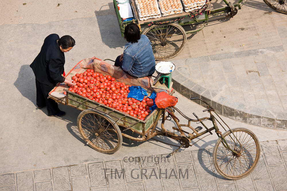 Tomatoes and eggs for sale from carts in street market, viewed from the City Wall, Xian, China