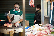 A butchers chops a carcass of meat for a woman customer in the Athens Central Market on Athinas Street. Athens, GreeceA butchers chops a carcass of meat for a woman customer in the Athens Central Market on Athinas Street. Athens, Greece