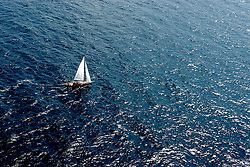 A sailboat navigate on the Adriatic sea in south Italy.