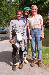 Multiracial family standing outdoors smiling,