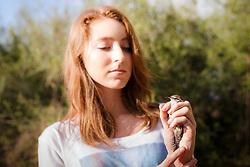 Woman  holding bird before releasing after bird banding and measurement, Mitchell Lake Audubon Center, San Antonio, Texas, USA.