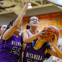 Gallup Bengal Ashley Antone (1) reaches over Miyamura Patriot Brittany Charley (34) for a rebound Monday at Gallup High School.