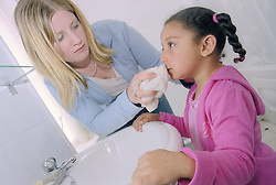 Single mother in the bathroom giving her young daughter a wash with a flannel,