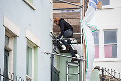 © Licensed to London News Pictures; 19/02/2021; Bristol, UK. People at house No. 63 are seen and heard doing work behind sheeting and scaffolding covering the mural, 'Aachoo', by Banksy showing a woman coughing out her dentures on the house wall on the corner of Park Street and Vale Street, Totterdown, during the Covid-19 coronavirus pandemic in England. The house was in the process of being sold when the mural was painted on 10 December 2020. From social media it appears the protective measures were installed on 23 January 2021. With a roughly 22-degree gradient incline, Vale Street in the Totterdown area of Bristol is said to be England's steepest street. Photo credit: Simon Chapman/LNP.
