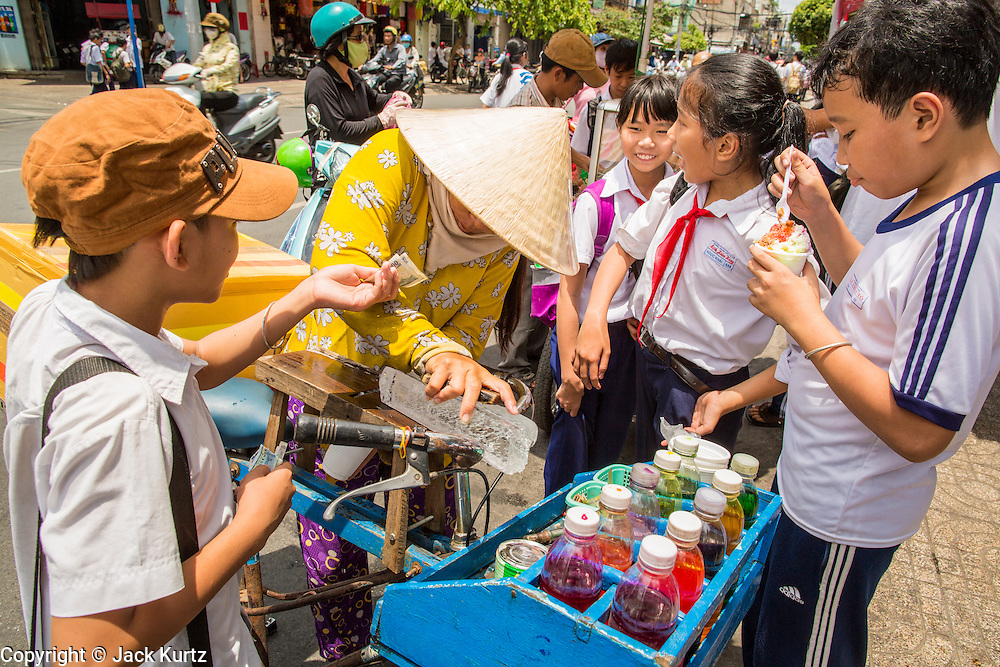 """12 APRIL 2012 - HO CHI MINH CITY, VIETNAM:  Schoolchildren buy shaved ice from a vendor in Cholon, the Chinese-influenced section of Ho Chi Minh City (former Saigon). It is the largest """"Chinatown"""" in Vietnam. Cholon consists of the western half of District 5 as well as several adjoining neighborhoods in District 6. The Vietnamese name Cholon literally means """"big"""" (lon) """"market"""" (cho). Incorporated in 1879 as a city 11km from central Saigon. By the 1930s, it had expanded to the city limit of Saigon. On April 27, 1931, French colonial authorities merged the two cities to form Saigon-Cholon. In 1956, """"Cholon"""" was dropped from the name and the city became known as Saigon. During the Vietnam War (called the American War by the Vietnamese), soldiers and deserters from the United States Army maintained a thriving black market in Cholon, trading in various American and especially U.S Army-issue items.         PHOTO BY JACK KURTZ"""