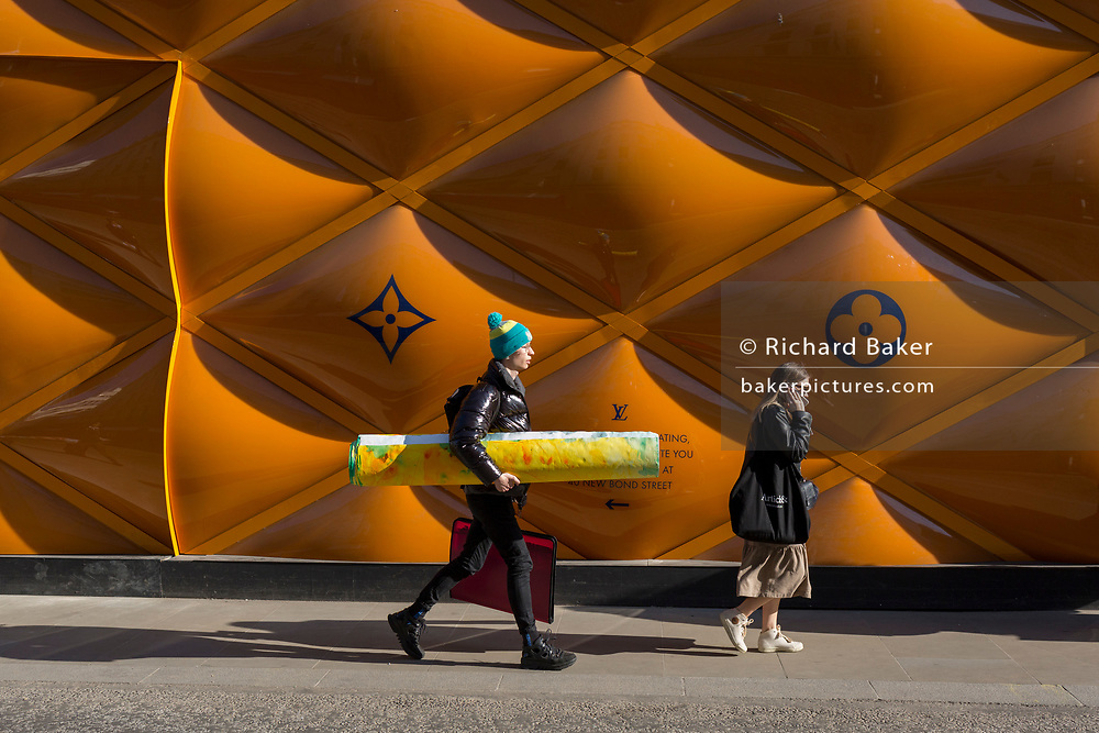 An artistic man carrying an artwork under his arm walks past the temporary renovation hoarding of luxury brand Louis Vuitton in New Bond Street, on 27th February 2019, in London, England.