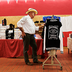 Un homme regardent des vêtements en vente lors d'une soiree de danse et concert country organisee par l'association Hell's Boots. Villeneuve-Saint-Germain, France. 17 novembre 2019. <br /> A man looking at clothes on sale during a country dance & concert night, held by the Hell's Boots association. Villeneuve-Saint-Germain, France. November 17, 2019.