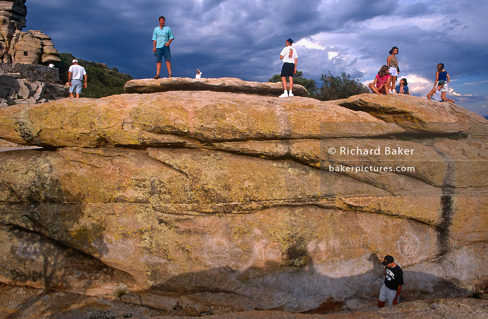 Visitors stand on graffiti-covered ancient rocks in Saguaro National Park, outside of Tucson Arizona.