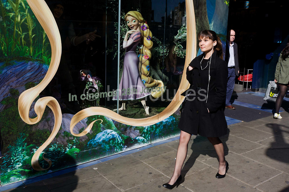 A Disney character Rapunzel from their film Tangled stands looking at women, exemplifying feminine beauty. The smaller than life-size model of the Disney character Rapunzel from their company's film called Tangled stands in the window of their London store, seemingly looking out in admiration and delight at a young elegant woman wearing black. Advertising the forthcoming opening of the movie, the display of the central character exemplifies feminine health, beauty, and inadvertently, of American or white European values. The woman walks past oblivious at the attention that this fictitious person is affording them – her own lifestyle being an everyday personal choice of style and a statement about femininity and gender on this urban street.