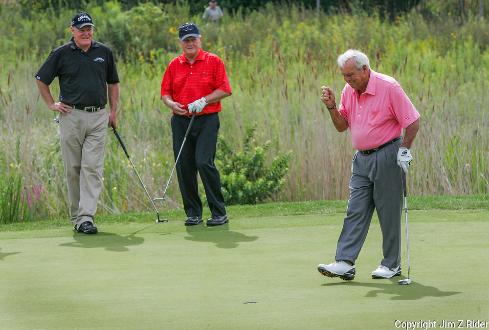 Arnold Palmer, who was paired with Jack Nicklaus, center, for the first six holes, celebrates sinking a putt on the front nine at the Golf Club at Harbor Shores in Benton Harbor, Michigan.  The two legends joined Johnny Miller, left, and Tom Watson for Champions For Change, which was 18 holes of a scramble skins format with rotating two-man teams to commemorate the opening of the Jack Nicklaus Signature course.  Some holes on the course wind through sand dunes providing views of Lake Michigan.  The course hosted the 2012 and 2014 Senior PGA Championship.