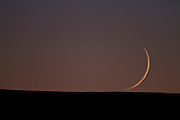 Crescent moon setting over the Red Desert of Wyoming