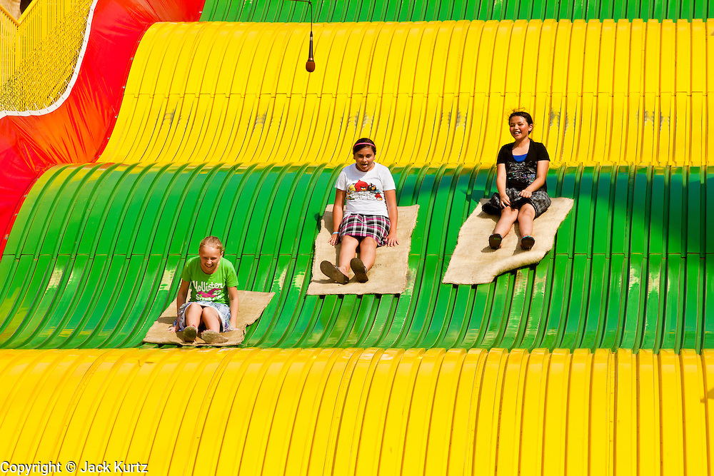 """01 SEPTEMBER 2011 - ST. PAUL, MN:  People ride the Giant Slide at the Minnesota State Fair. The Minnesota State Fair is one of the largest state fairs in the United States. It's called """"the Great Minnesota Get Together"""" and includes numerous agricultural exhibits, a vast midway with rides and games, horse shows and rodeos. Nearly two million people a year visit the fair, which is located in St. Paul.  PHOTO BY JACK KURTZ"""