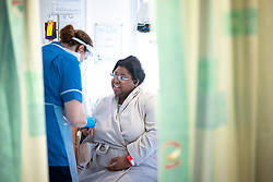 © Licensed to London News Pictures . 18/08/2021. Manchester , UK . Ward Sister DANIELLA POSTLE (27 from Bury) at the bedside of patient NATALIE BAKER (40 from Ardwick) . Clinicians treat patients for the effects of Coronavirus , on the Covid Cohort Ward at Manchester Royal Infirmary . The ward is made up of 28 beds and has been converted from what was a urology ward for the purpose of treating Covid positive patients . Photo credit : Joel Goodman/LNP