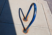 A bike rack casts a shadow to form a heart on the pavement in Boulder, Colorado.