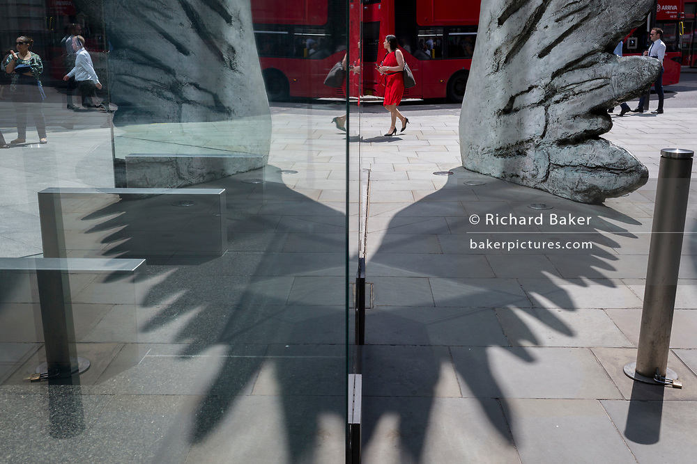 A financial industry businesswoman in red walks past the sculpture entitled City Wing on Threadneedle Street in the City of London, the capital's financial district (aka the Square Mile), on 11th July 2019, in London, England. City Wing is by the artist Christopher Le Brun. The ten-metre-tall bronze sculpture is by President of the Royal Academy of Arts, Christopher Le Brun, commissioned by Hammerson in 2009. It is called 'The City Wing' and has been cast by Morris Singer Art Founders, reputedly the oldest fine art foundry in the world.
