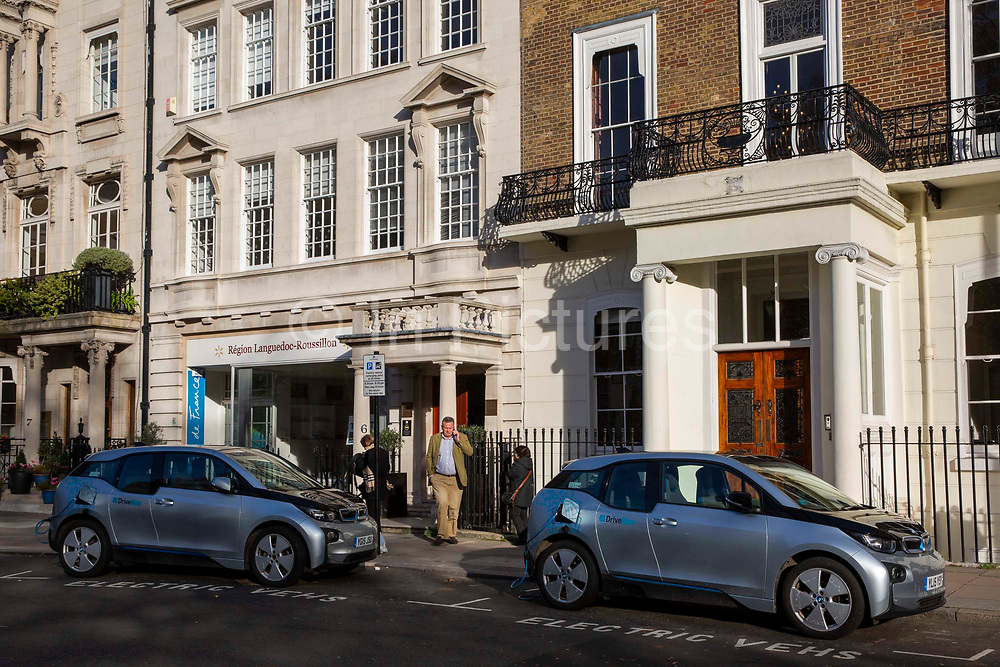 A man walkes between two BMW i3 electric cars charging in an electric vehicle bay on Cavendish Square, central London, United Kingdom. The POLAR charging Network has over 6,000 charging points across the United Kingdom.