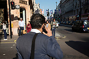 Man seen from behind on his mobile phone in London, United Kingdom.