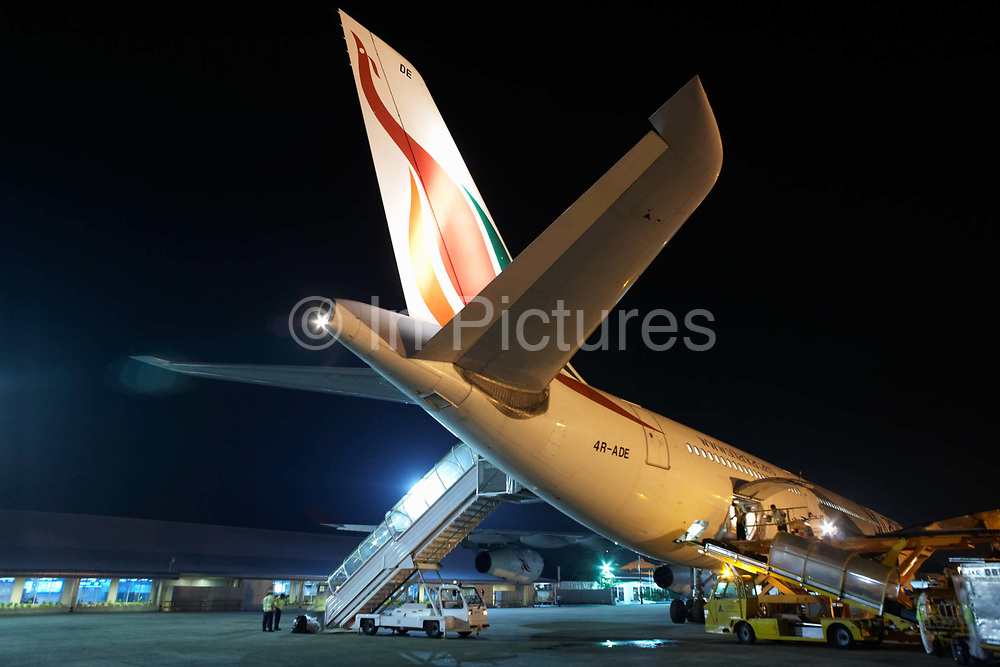 One a hot November night, a Sri Lankan Airlines A340-300 series Airbus - registration number 4R-ADE - is bathed in high-intensity floodlights on the apron at Malé international airport in the Republic of the Maldives. Surrounded by passenger steps, servicing vehicles for catering and the loading of baggage and air freight in the below-floor holds, the aircraft is readied for its next flight to Colombo, another journey for this aircraft as it travels across the world's air routes.