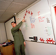 Squadron Leader Dunc Mason of the Red Arrows, Britain's RAF aerobatic team instructs new manoeuvres to others.  <br /> Flt. Lt. Dave Mason shows the finer points of an aerobatic manoeuvre in the crew briefing room. They will soon be putting this formation into practice in the air of their RAF Scampton airspace. Using magnetic models of Hawk jet aircraft Mason shows how their formation is to be flown on their next training flight. Five autumn and winter months are spent teaching new recruits manual aerobatic display flying while the older members (who rotate positions) learn new disciplines within the routine. Their leaning curve is steep, even for these accomplished fast-jet aviators who had already accumulated 1,500 hours in fighters. By Summer they need every aspect of their 25-minute displays honed to perfection.