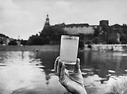Szklanaka wody pobranej z Wisły na tle Wawelu. Lata 80. XX wieku