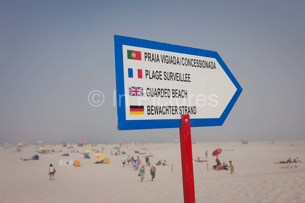 A warning sign in four languages telling sea swimmers of the dangers on this Portuguese beach that only one side is guarded by lifesavers, on 18th July 2016, Costa Nova, near Aveira, Portugal. The Portuguese, French, English and German writing should inform most of those thinking of entering the rough waters, especially with mist rolling in.