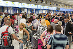 © Licensed to London News Pictures . 24/06/2014 . Manchester Airport , UK . Crowds of travellers queue at the check in desks for departure at Manchester Airport's Terminal 1 as England's early exit from the World Cup sees holiday makers snap up late deals on holidays abroad  . Photo credit : Joel Goodman/LNP