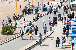 © Licensed to London News Pictures. 16/05/2020. Brighton, UK. Members of the public take to the beach and promenade in Brighton and Hove as the lock down is relaxed across the UK. A queue forms outside a bar that provides drinks for take away. Photo credit: Hugo Michiels/LNP
