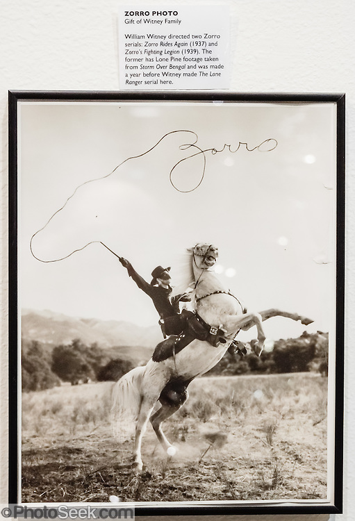 Zorro rears his white horse and his whip magically spells Zorro cursively in the air, in this photograph gifted by the Witney Family to the Beverly and Jim Rogers Museum of Lone Pine Film History. Director William Witney directed two Zorro serials: Zorro Rides again (1937) and Zorro's Fighting Legion (1939). Zorro (Spanish for fox) is the secret identity of Don Diego de la Vega, a fictional character created in 1919 by New York-based pulp writer Johnston McCulley. Zorro is a Californio nobleman of Spaniard and Native Californian descent, living in Los Angeles during the era of Spanish rule. The character has been featured in numerous books, films, television series, and other media. The typical image of him is a dashing black-clad masked outlaw who defends the commoners and indigenous peoples of the land against tyrannical officials and other villains. Not only is he too cunning and foxlike for the bumbling authorities to catch, but he also delights in publicly humiliating them. / In 2015, this fascinating museum (where this Zorro photo is hung) was renamed the Museum of Western Film History. Visit it at 701 S. Main Street, Lone Pine, California, 93545, USA. Web site: www.lonepinefilmhistorymuseum.org