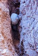 A single river rock wedged into a canyon crevice along the Colorado River.