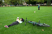 London Fields, public park. Woman lying down on the grass reading next to her bicycle.