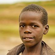 A young boy poses for a portrait near the dried up water source of Burega Pond, Rulindo District, Rwanda.