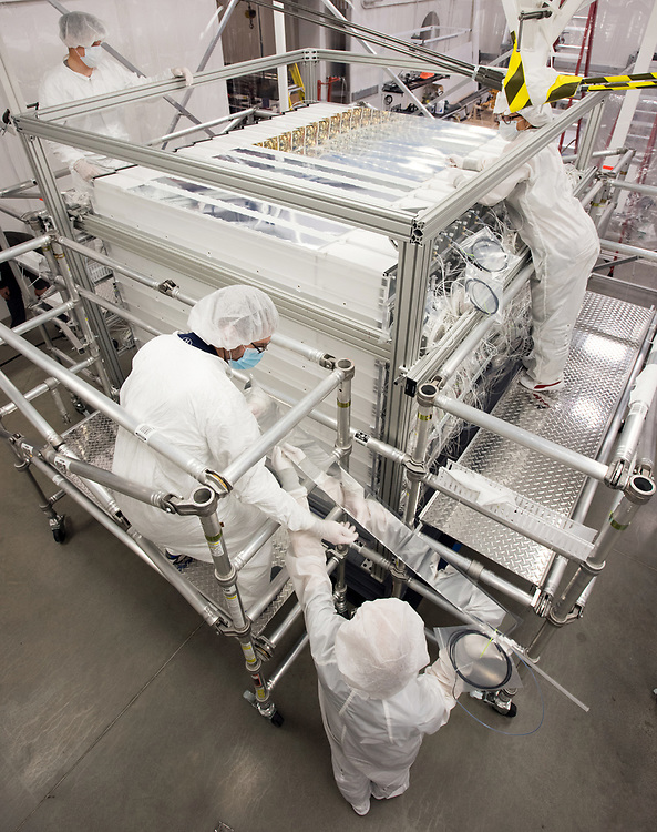Photo by Mara Lavitt<br /> New Haven, CT<br /> November 17, 2017<br /> Photography: ©Mara Lavitt<br /> <br /> The final stages of building a neutrino detector at Yale University's Wright Lab. From left: Temple University Research Assistant Professor Don Jones, Temple University Research Engineer James Wilhelmi receiving a reflector from Yale Postdoctoral Researcher Tom Langford, Yale graduate student Danielle Norcini.