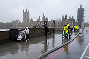Pedestrians and workmen cross Westminster Bridge on a wet, rainy day opposite the Palaces of Westminster, on 21st October 2020, in London, England.