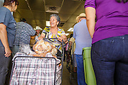 07 AUGUST 2012 - TOLLESON, AZ:    Clients leave after picking up meals at the food bank in Tolleson, AZ, about 15 miles west of Phoenix. The Tolleson food bank has been operating for more than 20 years. It used to serve mostly the families of migrant farm workers that worked the fields around Tolleson but in the early 2000's many of the farms were sold to real estate developers. Now the food bank serves both farm worker families and people who lost their homes in the real estate crash, that his Phoenix suburbs especially hard. More than 150 families a day are helped by the Tolleson food bank, an increase of more than 50% in the last five years.   PHOTO BY JACK KURTZ