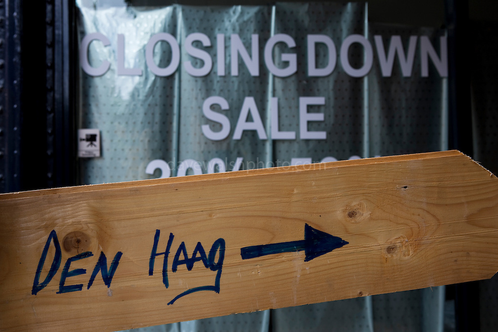 """Wooden Den Haag sign, with """"closing down"""" sale behind"""