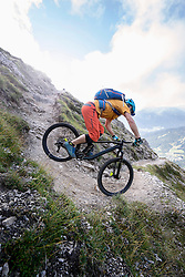 Mountain biker rides a narrow curve downhill, Tirol, Austria