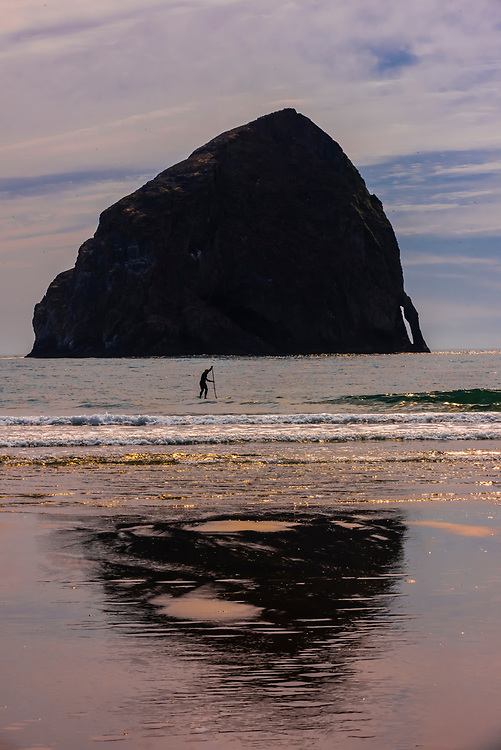 A man stand up paddleboarding with Haystack Rock behind, Cape Kiwanda, near Pacific City, Oregon USA.