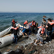 A group of Syrian refugees, among them a disabled man carried by his compatriots and locals,  the moment they disembark from their small inflatable boat and land to Europe, on the beach of Skala Sykaminias. Everyday hundreds of refugees, mainly from Syria and Afghanistan, are crossing in small overcrowded inflatable boats the 6 mile channel from the Turkish coast to the island of Lesbos in Greece. Many spend their life savings, over $1000, to buy a space on those boats.
