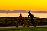 Riding bicycles at sunset (East Beach behind), Santa Barbara, California USA.