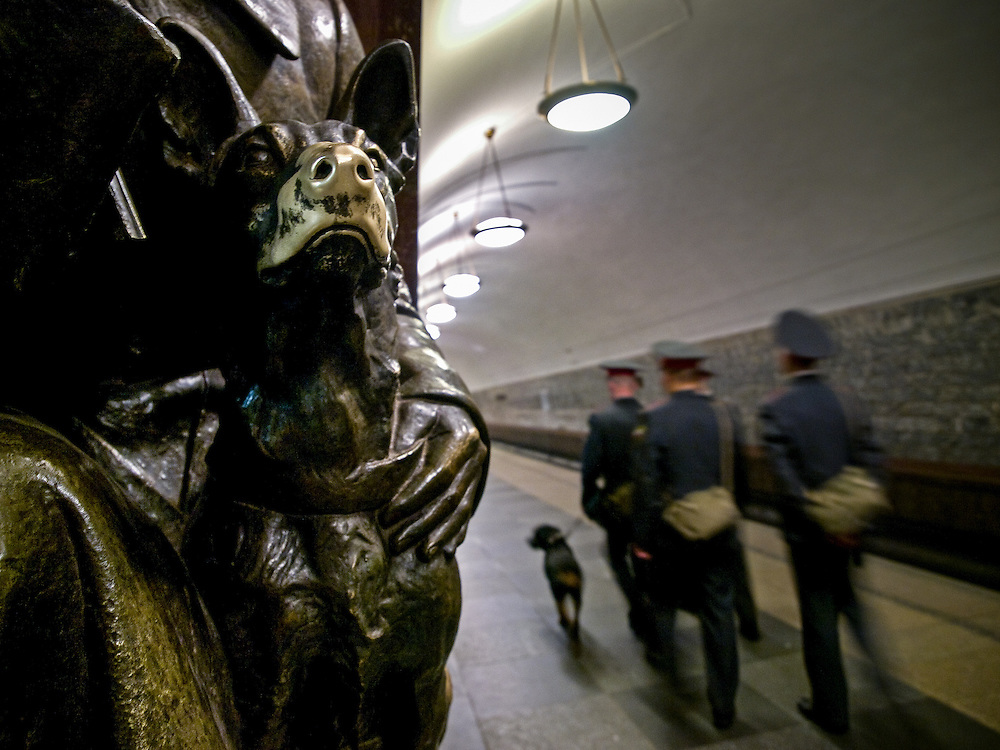 """Police with dog at the Moscow subway station """"Ploshchad Revoluyutsii"""" (Revolution Square) which is devoted to glorify the the lives, work and heroism of the ordinary men and women of the Russian Revolution. People are touching a dogs nose for a moment to be lucky and to fulfil a future wish."""