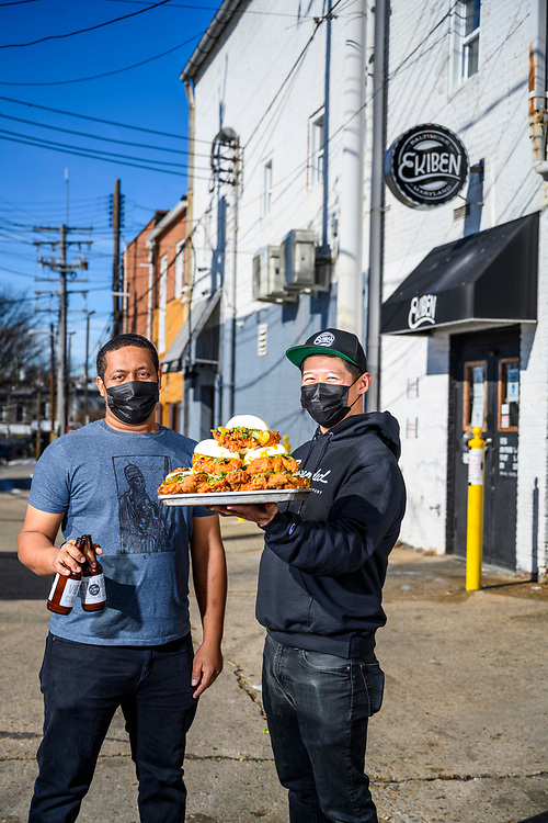 Baltimore, Maryland - February 04, 2021: Ekiben owners Ephrem Abebe, left, and Steve Chu, right, stand outside their second location in Hampden — with a tower of The Neighborhood Bird sandwiches and their bottled Vietnamese Cold Brew coffee Thursday February 4th, 2021. Abebe and Chu are two first-generation millennials and UMBC college grads who opened up their little Asian-fusion spot Ekiben in Fells Point, and found more success in a Hampden alleyway storefront. <br /> CREDIT: Matt Roth for Baltimore Magazine