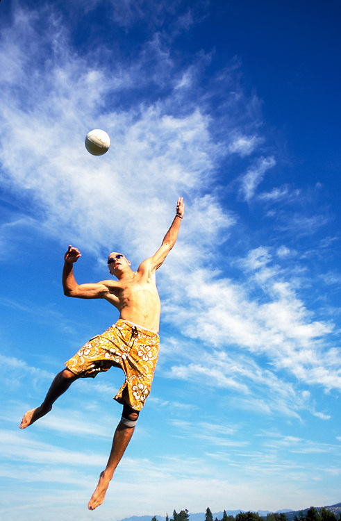 Young man delivering a jump serve while playing volleyball.