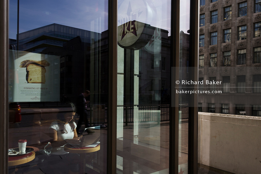 A lone businesswoman works on her laptop in a sunny and  provate corner of lunchtime restaurant chain Pret a Manger.
