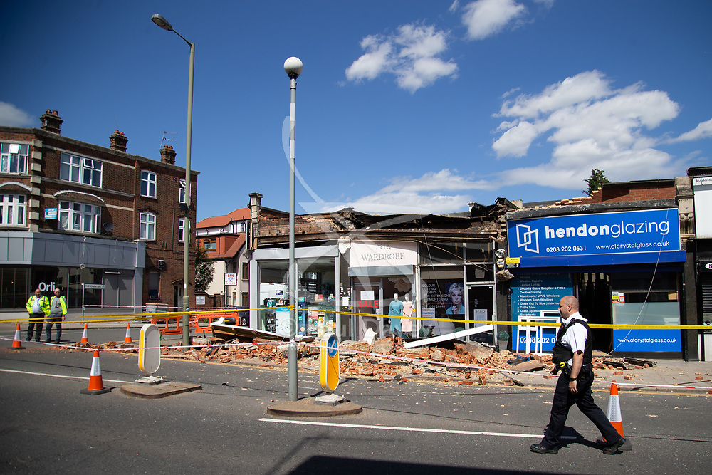 "A facade on a row of shops on Brent Street in Hendon has collapsed, causing police to close off the road whilst they make the site safe. No injuries were reported. According to the manager of the Hendon Glazing, Lucian Filote, 30, ""We were working in the shop as usual when we heard a loud bang. At first we thought it was a crash on the road but as we approached the shop entrance we saw the pile of rubble outside. Our first concern was that someone might have been hit by the falling bricks. We went and looked in the rubble but there was no one. We were concerned for our safety as there was a reinforcing bar with a lump of concrete hanging from it."" . Hendon, London, June 18 2018."