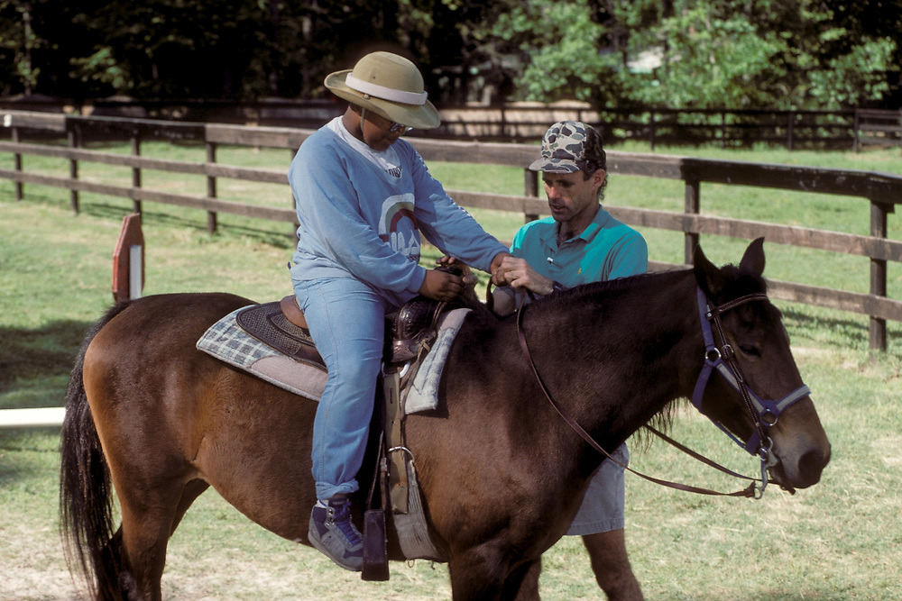 African-American 5th grade boy learning to ride horseback at an outdoor education camp.<br /> ©Bob Daemmrich/