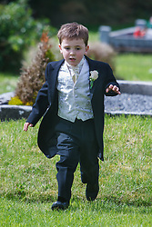 Child running through cemetery after wedding at Ballintubber Abbey, County Mayo, Ireland