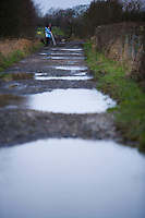 puddles in country lane with a photographer in the distance