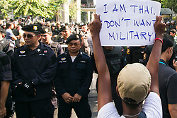 © Licensed to London News Pictures. 24/05/2014.An Anti-coup protestor  holds a sign in front of riot police reading 'I am thai i don't want military' following a Anti-Coup protest in Bangkok Thailand. The Royal Thai army announced a Military coup and have imposed a 10pm curfew.  Photo credit : Asanka Brendon Ratnayake/LNP