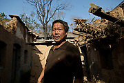 58 year old Qiao Jinchao stands in the courtyard that once belonged to his first uncle in Maijieping Village, near Dengfeng, Henan Province, China on 23 October,  2013. Once the home to some 200 people, the village of Maijieping has seen its numbers dwindled to only four permanent  residents as most have moved to more convenient locations with access to jobs, schools, and hospitals.
