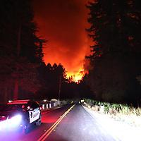 Santa Cruz County Sheriff's deputies patrol Highway 236 as a powerful blaze in the CZU August Lightning Complex roars along China Grade Road north of Boulder Creek, California on August 18, 2020.